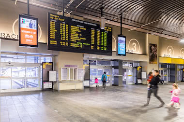 People walking by train departure board inside North Station