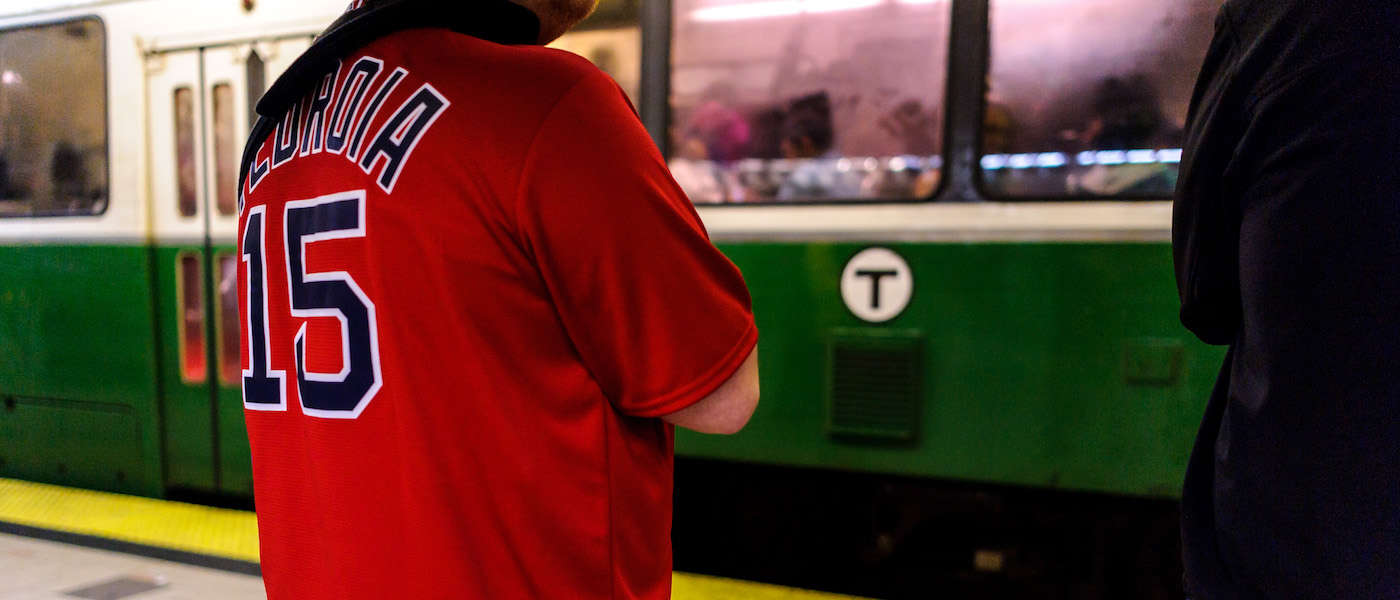 Man wearing a Red Sox jersey waits for a Green Line train