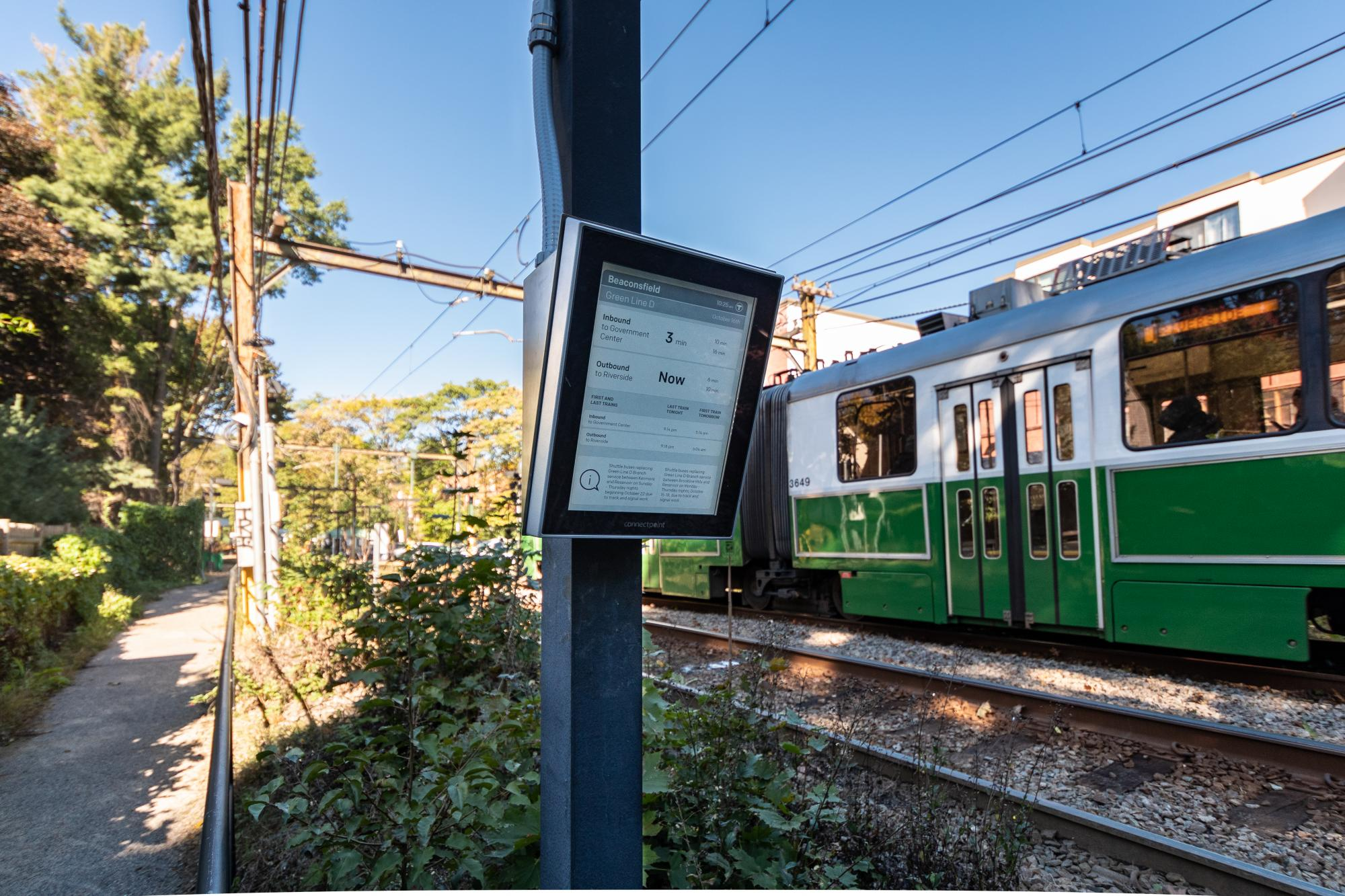 e-Ink sign on a pole, with a Green Line train in the background