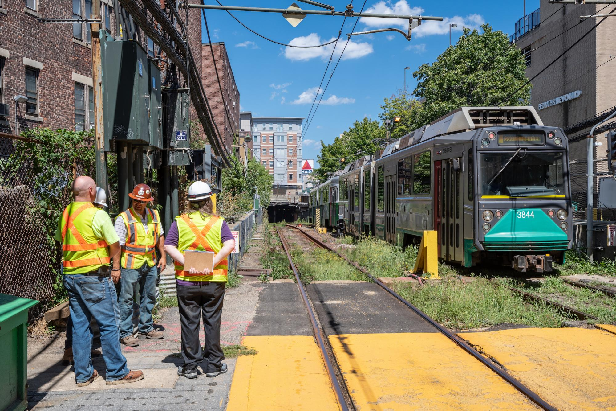 A crew at Fenway Station, as a Green Line train passes through