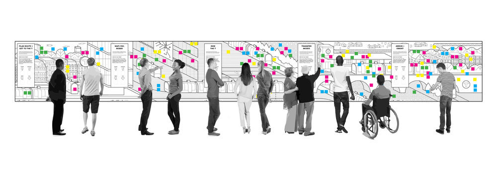 Ideation board with colorful sitcky notes and people in black and white in front of it.