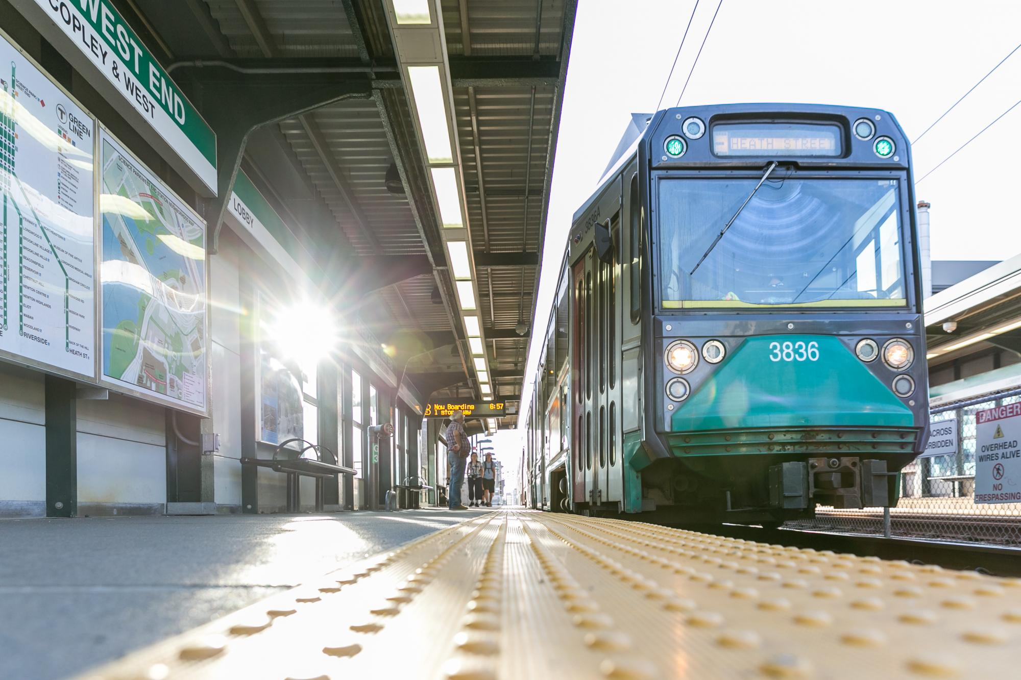 Green Line train pulls into Science Park/West End Station, with sunlight in the background.