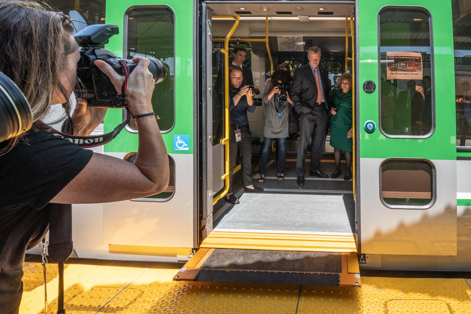 Gov. Charlie Baker and MassDOT Secretary Stephanie Pollack aboard a new Green Line train with bridge plate extended, at Riverside (July 2018)