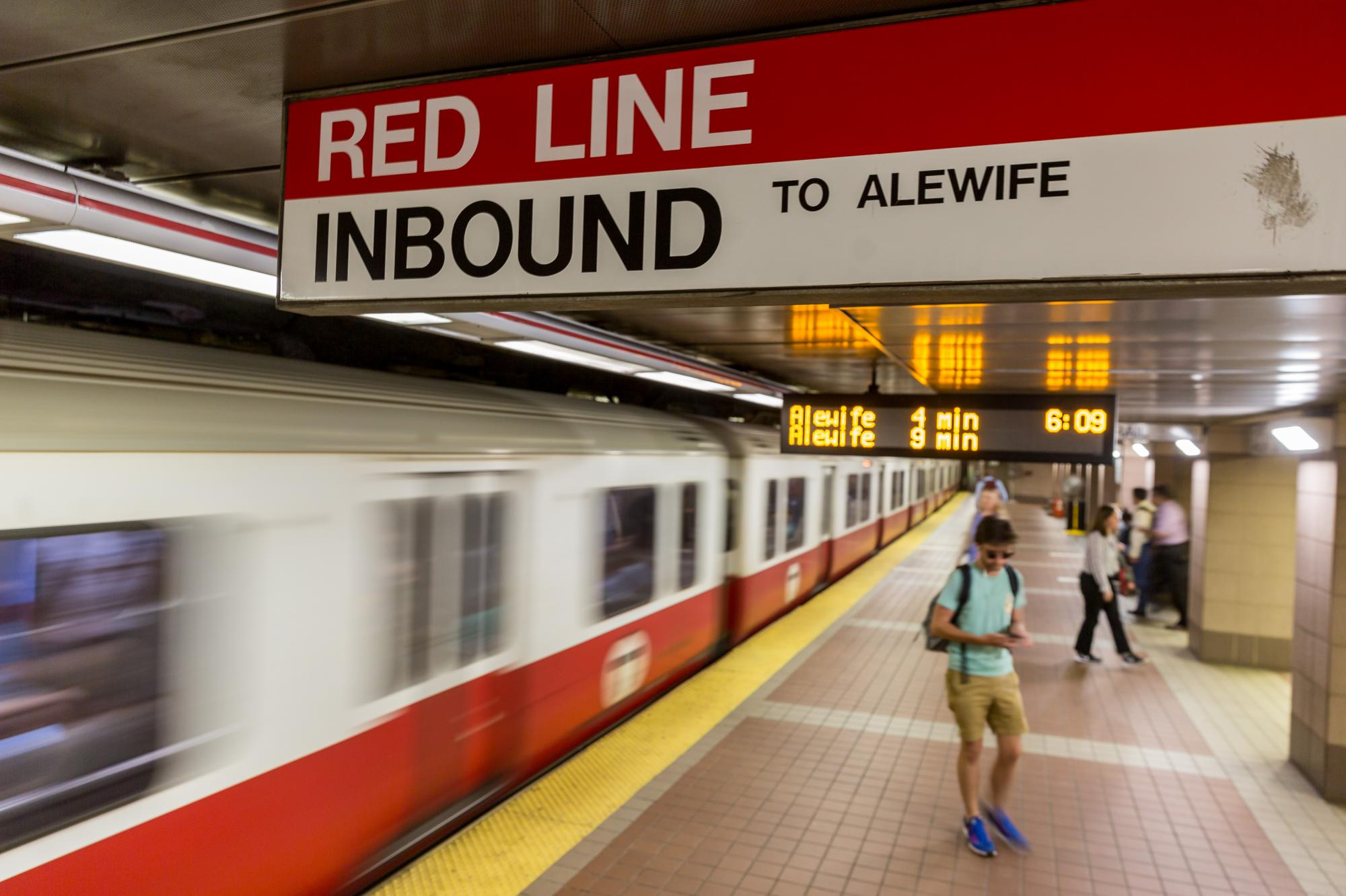 A Red Line train pulls out of the inbound platform at South Station, with passengers and a countdown clock in the background.