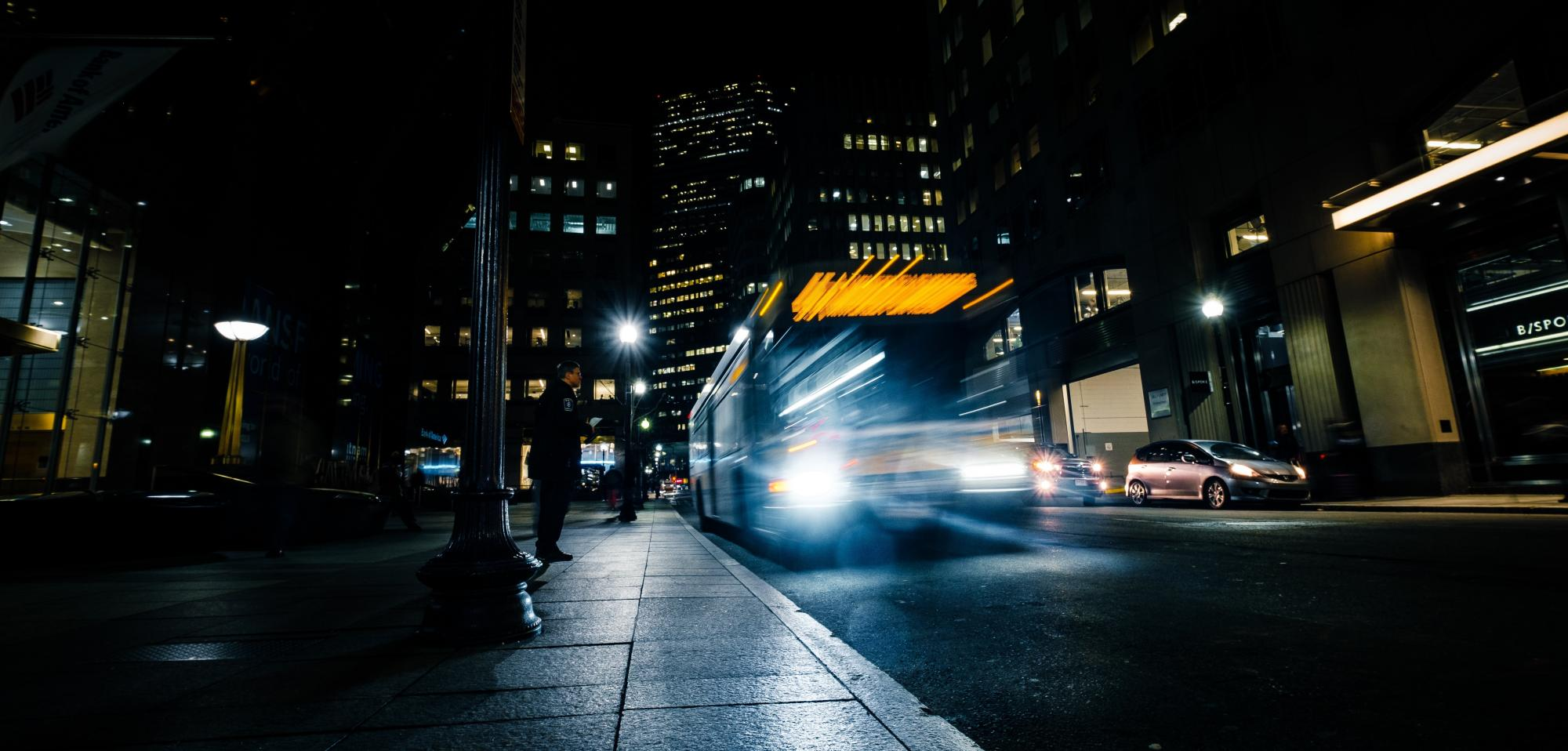 A bus at night in downtown Boston. Photo by Osman Rana, from Unsplash.