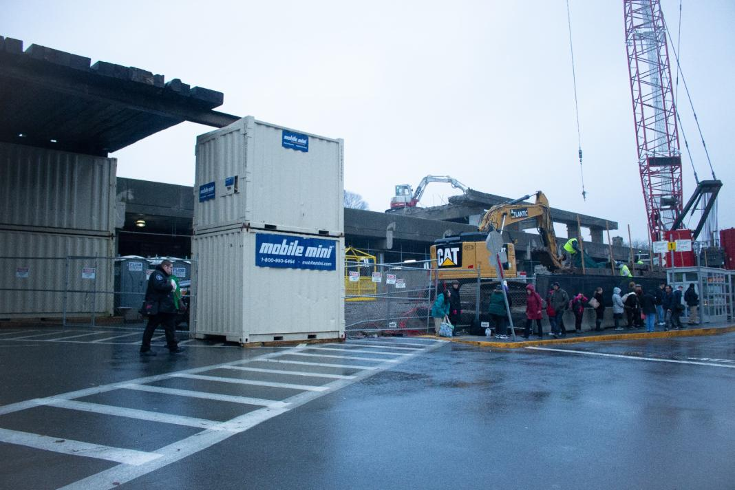 Passengers walk by equipment used for the Quincy Center garage demolition  (November 27, 2018)