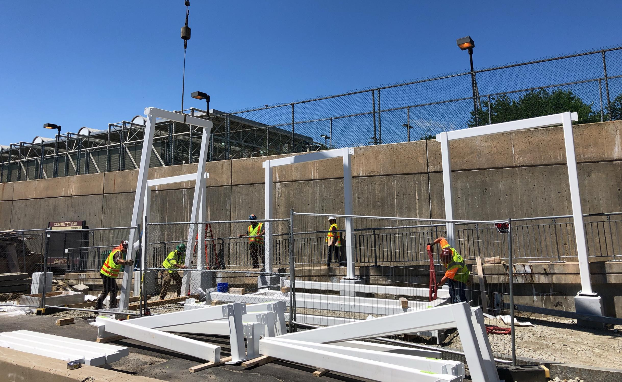 A crew assembles the canopy over the pedestrian ramp leading to the Commuter Rail platform.
