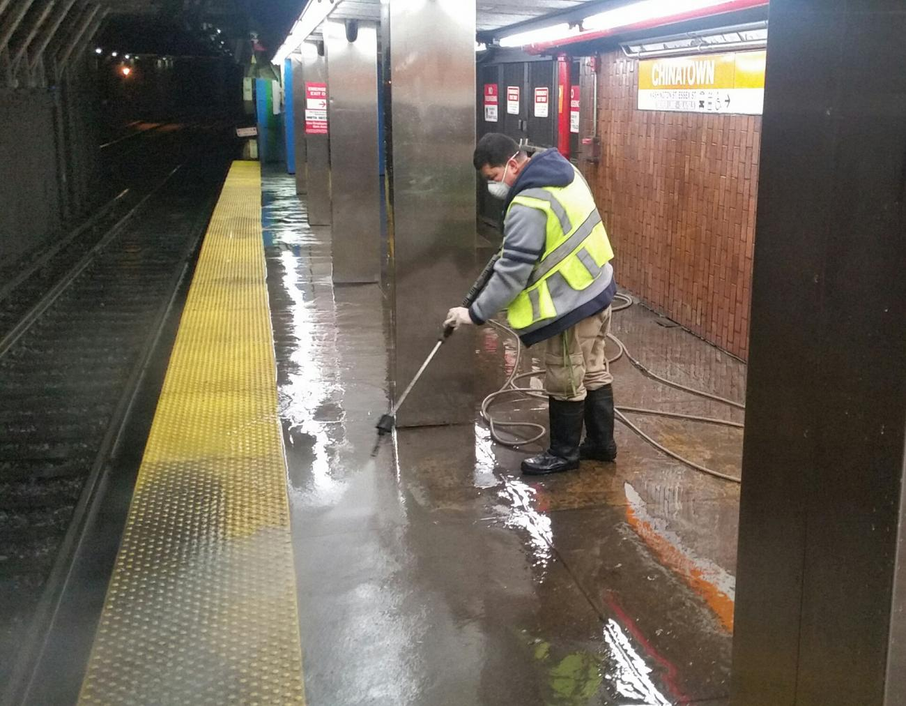 A worker sprays the platform at Chinatown