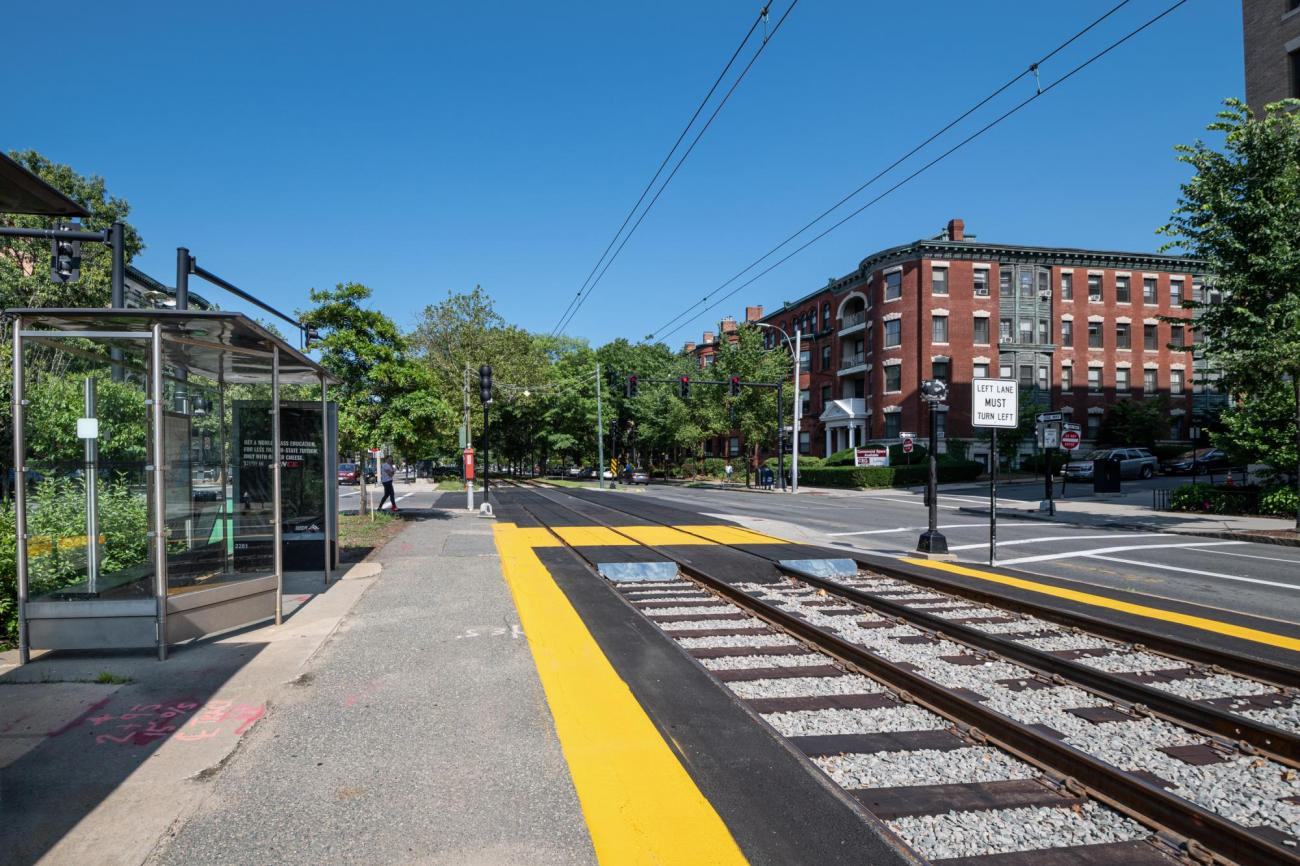 As viewed from the platform, a renovated intersection on the Green Line C branch, with a pedestrian crossing painted yellow and a yellow warning strip on the platform at Hawes St (July 2019).