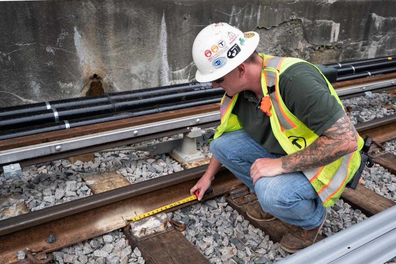 A crewperson crouches down to the track, using a tape measure to measure along the rail.