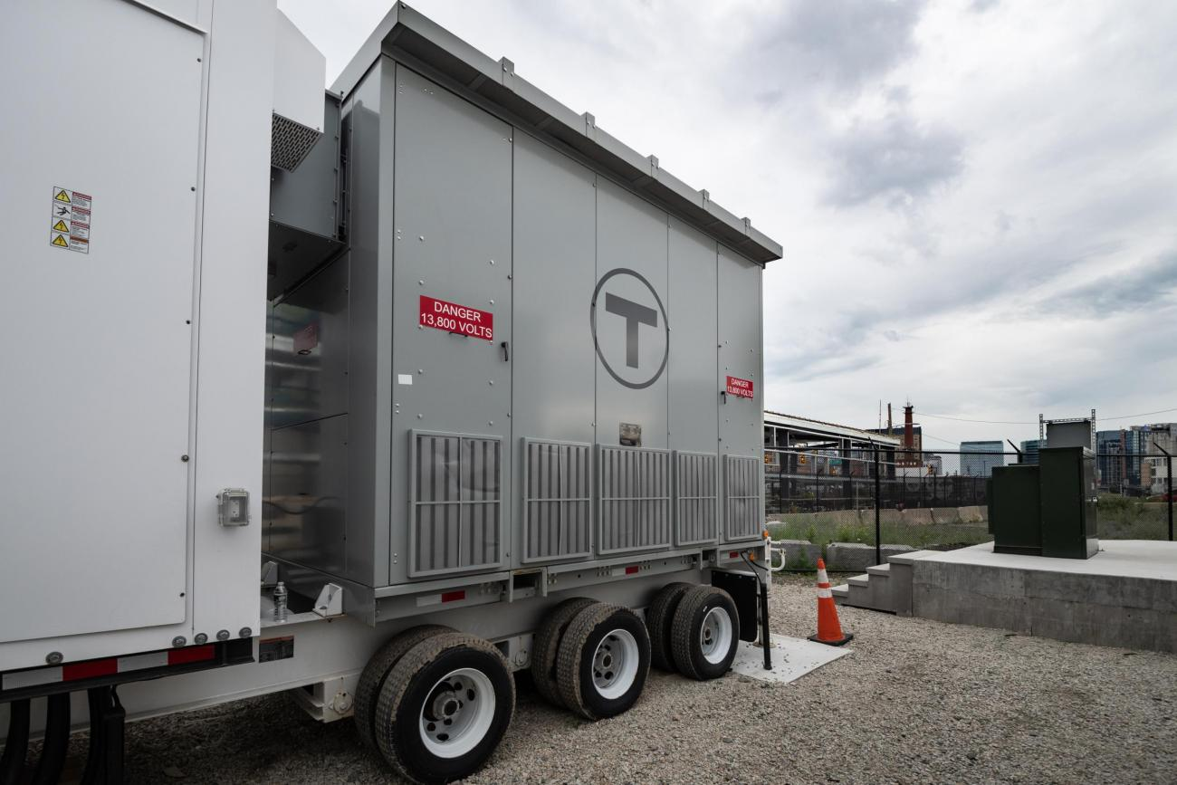 """A large portable generator, with a sign that reads """"Danger 13,800 Volts"""""""