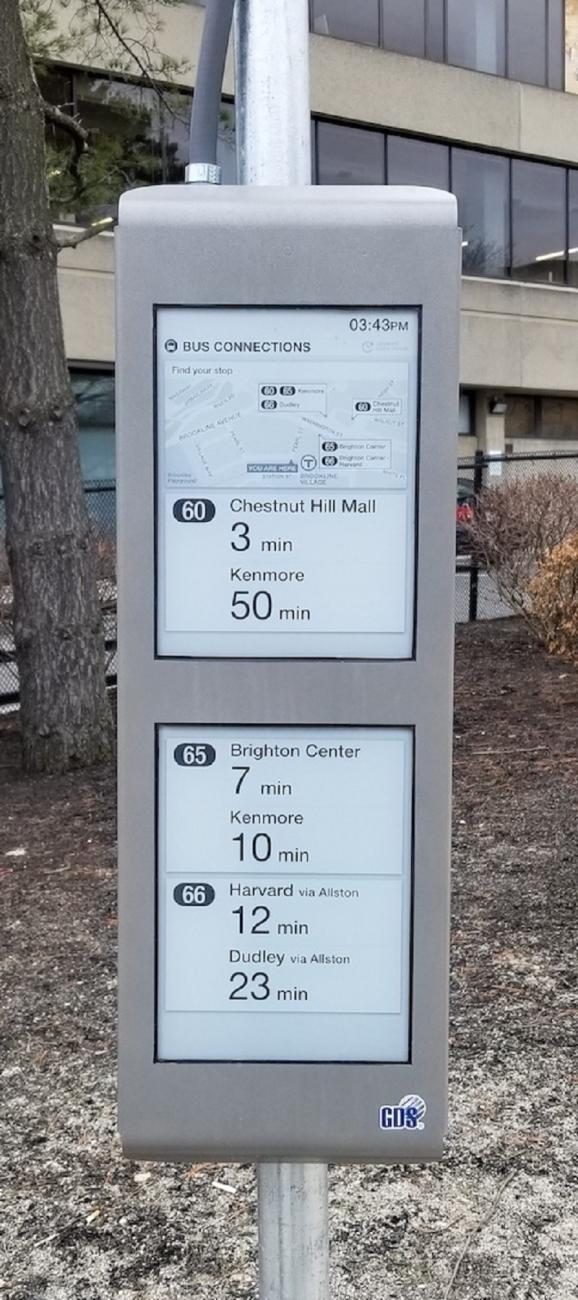 Close-up of an e-Ink sign displaying bus arrival times at Brookline Village