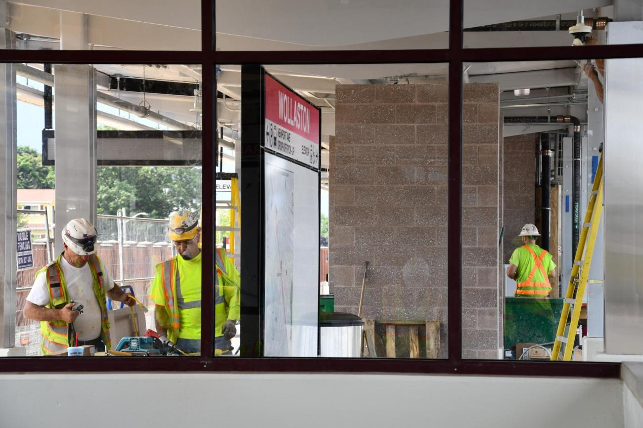 Viewed through a window, crews work at Wollaston Station during the final stages of renovation. (August 7, 2019)