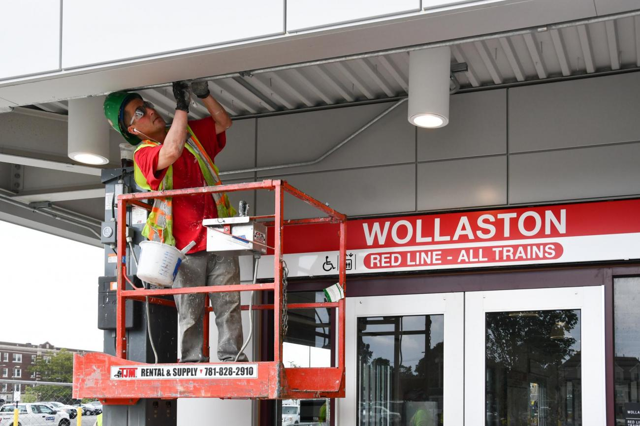 A crewperson on a lift works near the entrance to the renovated Wollaston Station. (August 7, 2019)