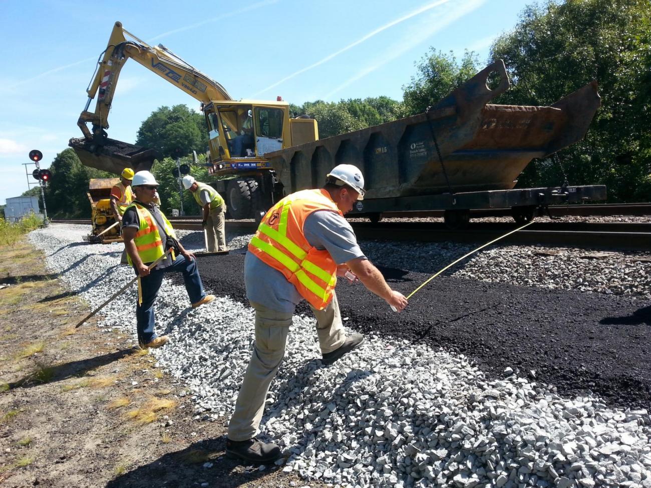 A worker lays asphalt parallel to the tracks, near the Merrimack River Bridge.