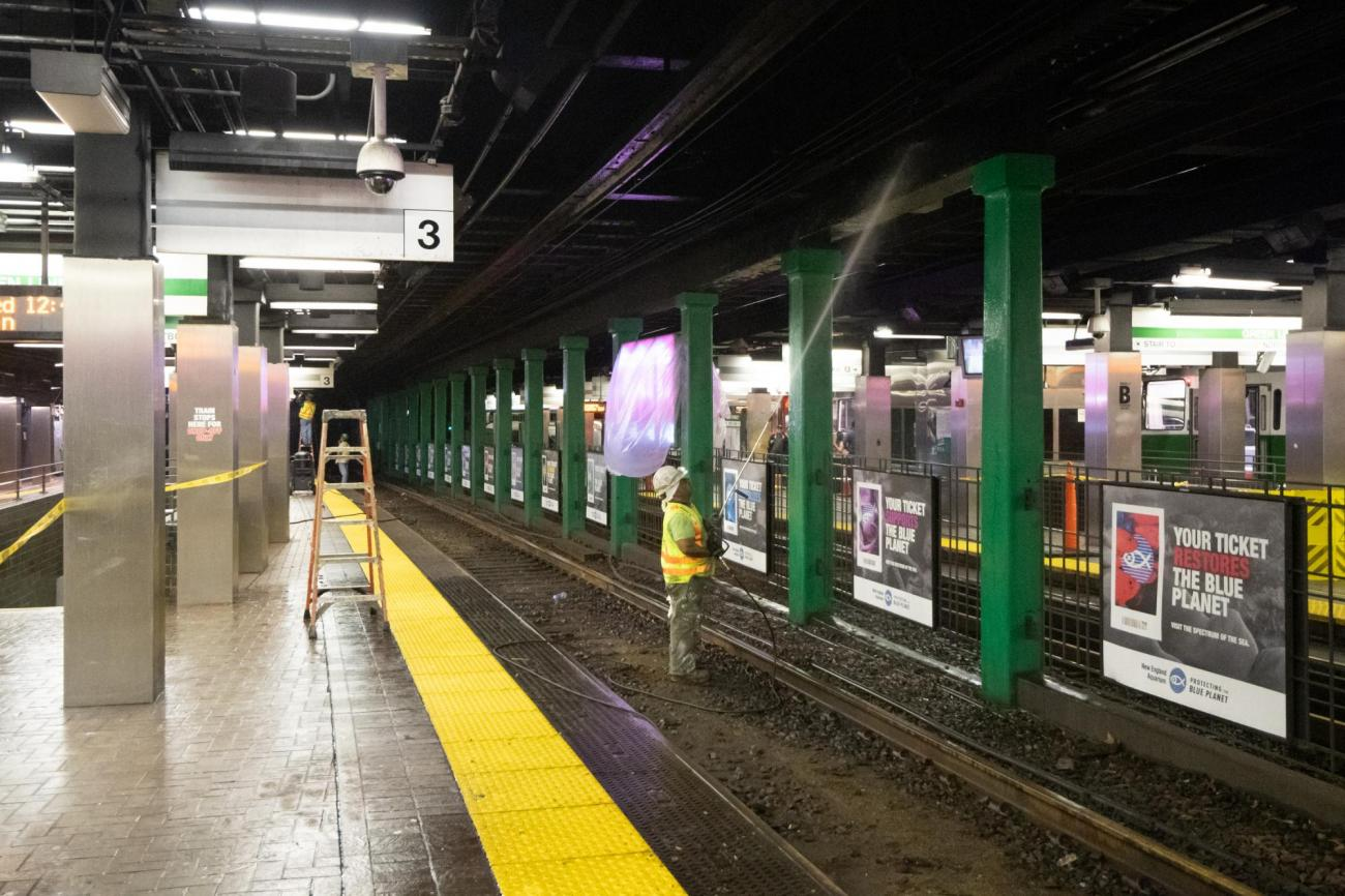 An MBTA worker cleans the ceiling above the Green Line platform at Park Street.