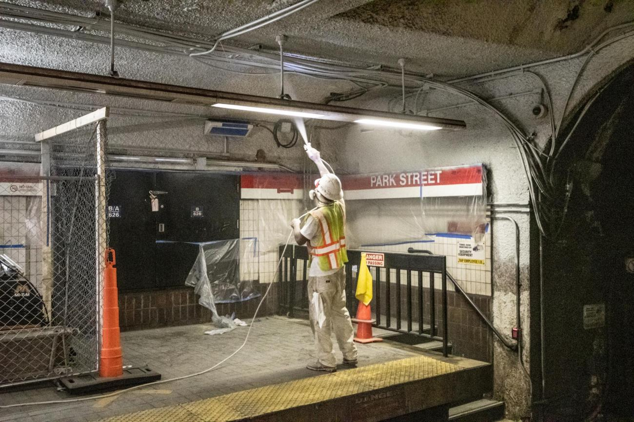 An MBTA worker cleans the ceiling above the Red Line platform at Park Street.
