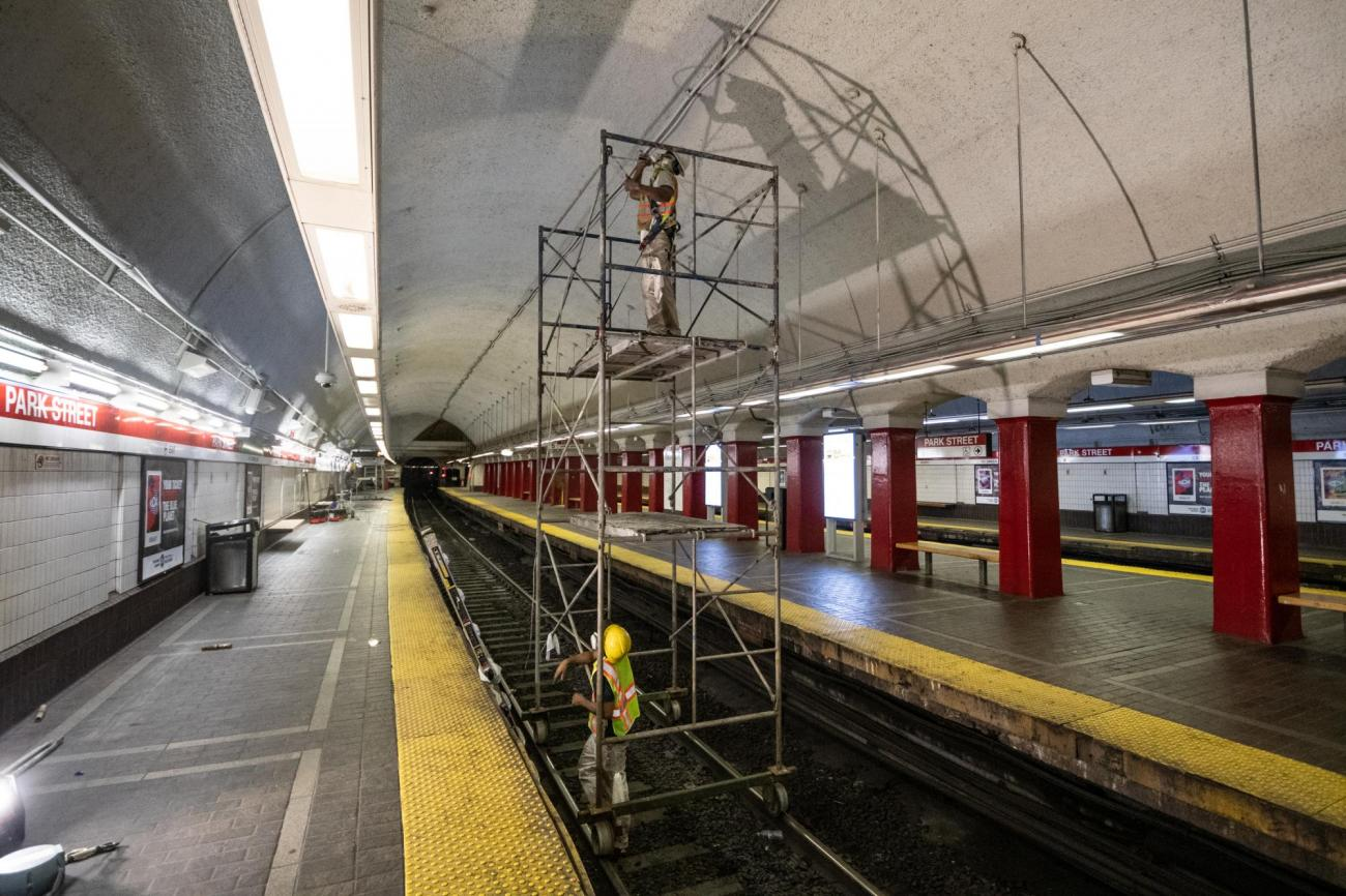 MBTA crews clean and repair the ceiling above the Red Line platform at Park Street Station