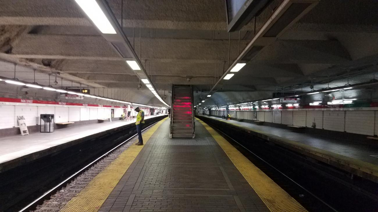 A worker stands on a platform at Park Street, where new LED light fixtures were installed on the Alewife platform in October 2019. Full lighting replacement is expected to be completed by December 2019.