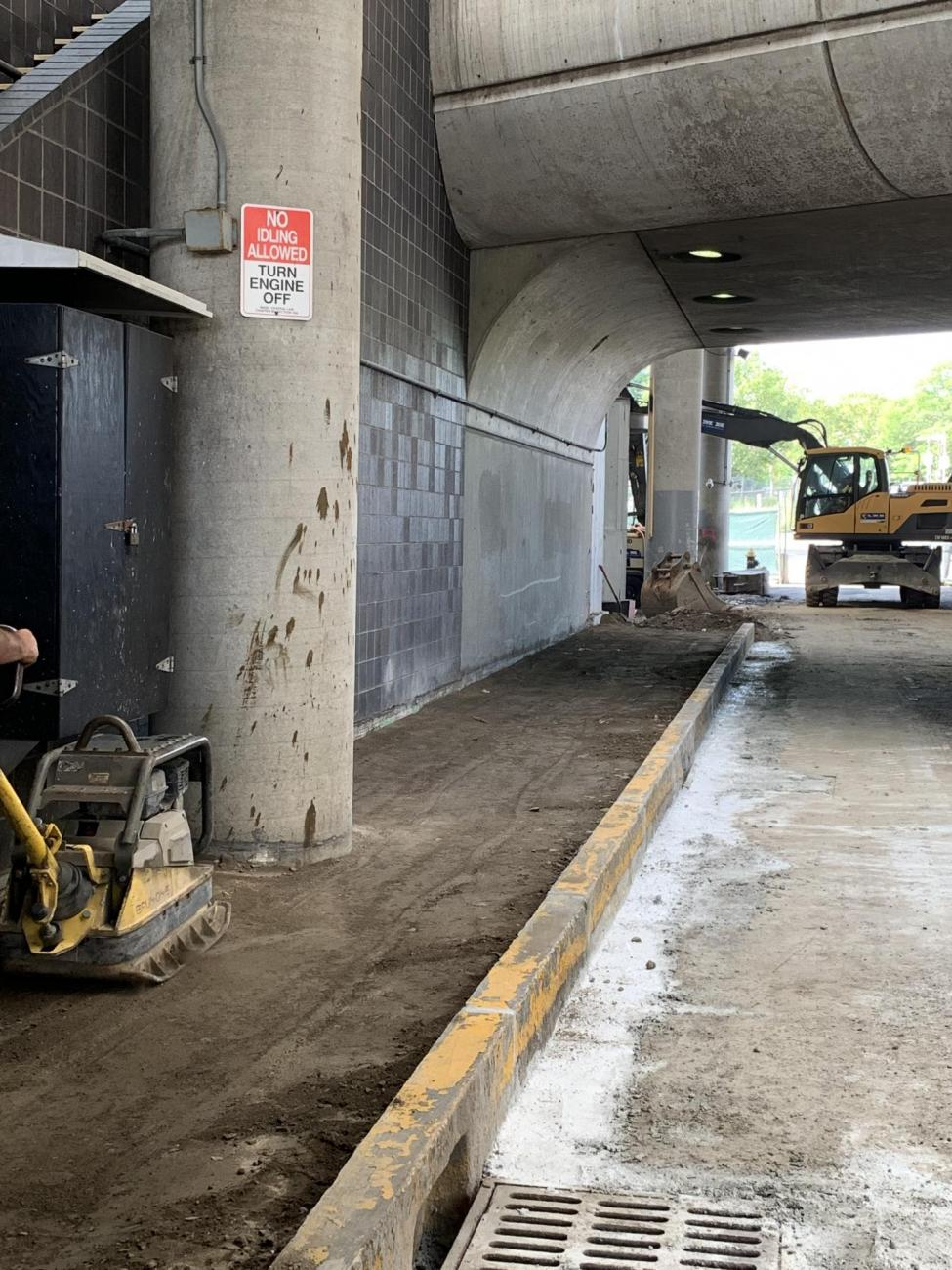 A crewmember prepares a sidewalk in the lower busway for new concrete