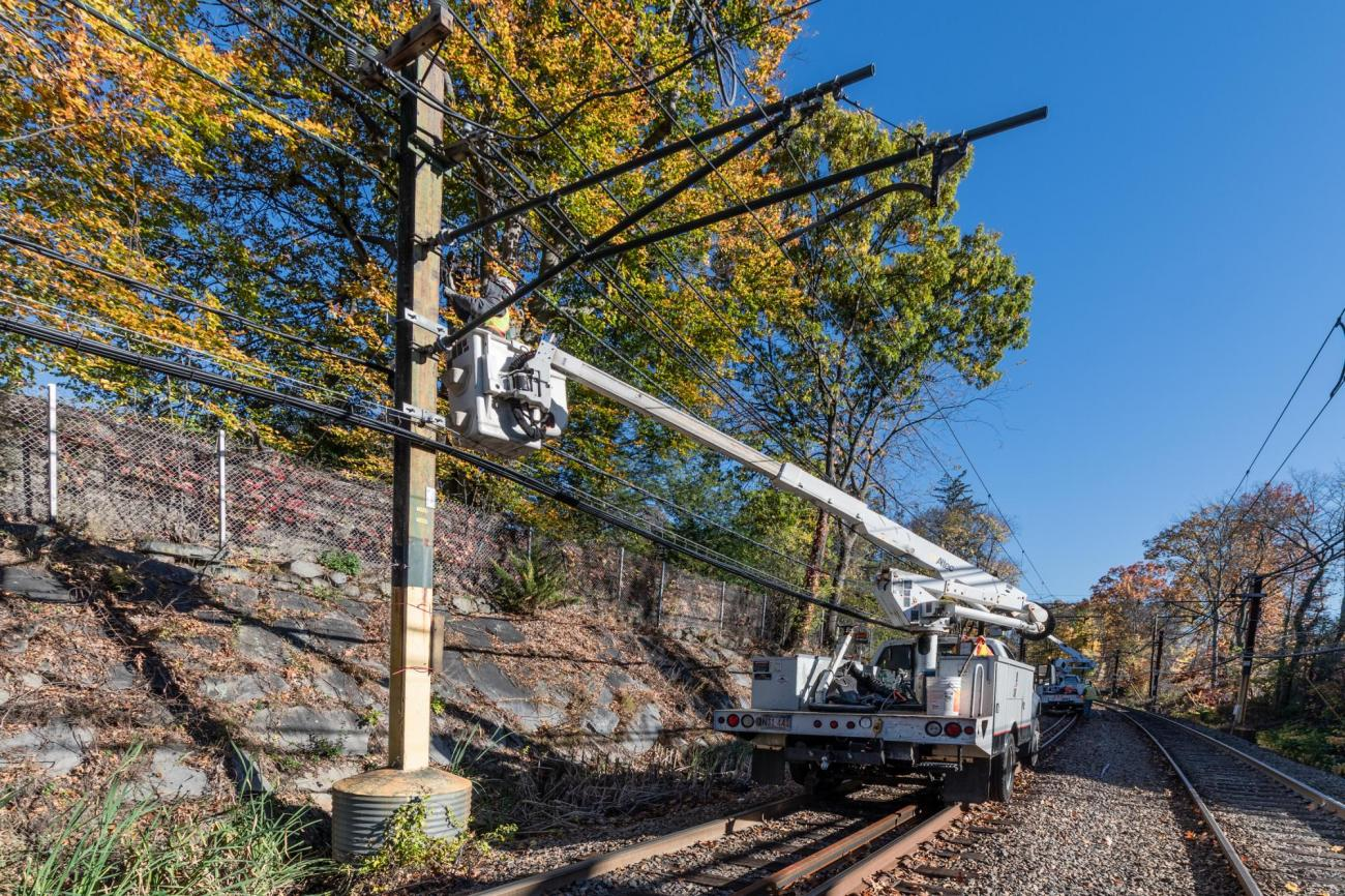 A crew uses a lift to work on signals near Chestnut Hill on the Green Line D branch.