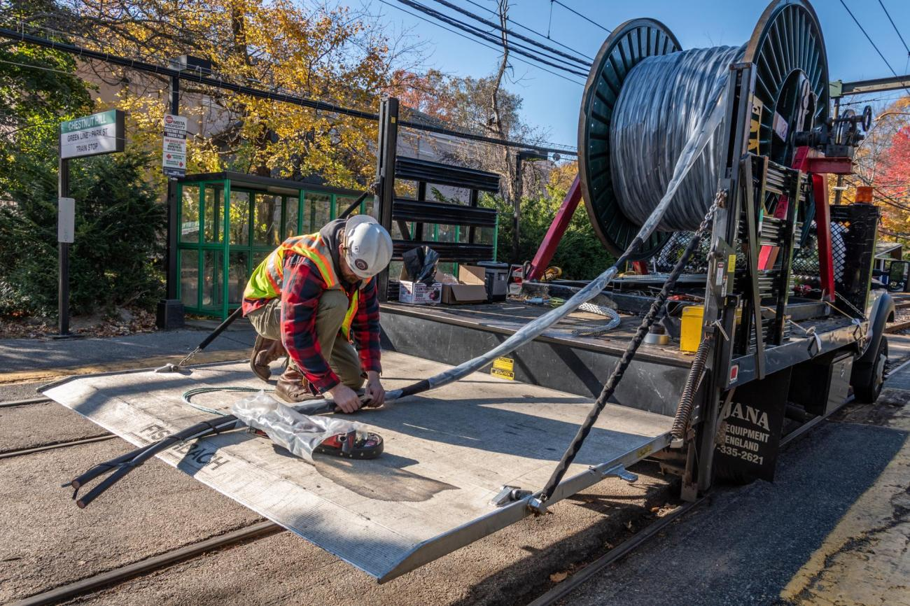 A crewman unwinds signal cable from a large spool, at Chestnut Hill on the Green Line D branch.