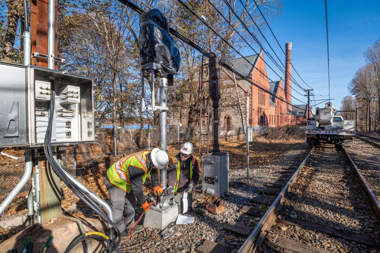 Two crewmen work on repairing a signal near Reservoir on the Green Line D branch.