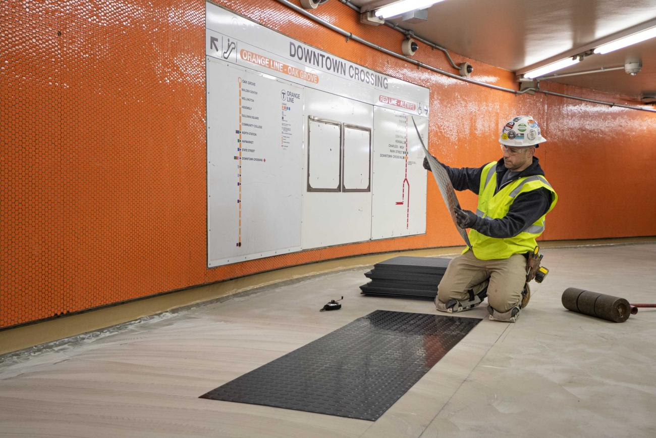 A crew member installs rubber flooring in Downtown Crossing's Alewife passage during the December 13 – 15, 2019, Red Line weekend shutdown