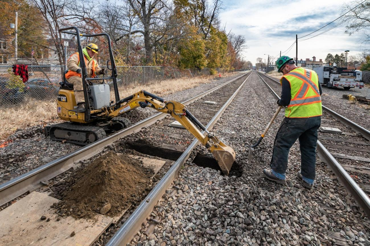 Crew members excavate under the track to prepare for power line installation as part of the PTC upgrades on the Lowell Line of the Commuter Rail (November 2019)