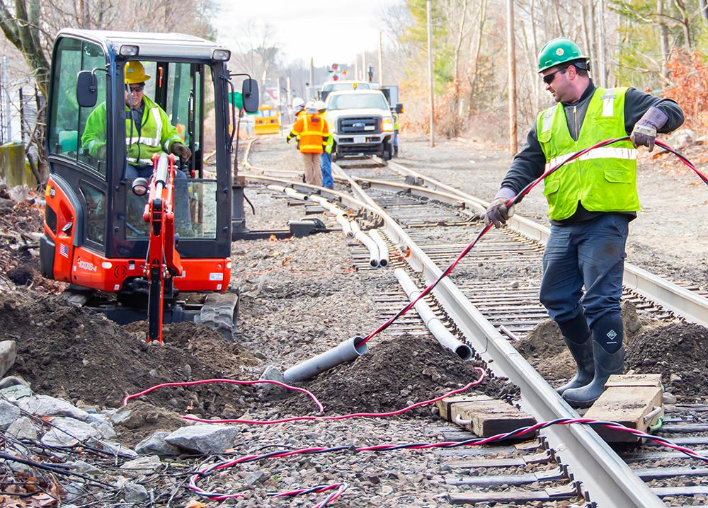 A crew installs track signal communication line near Walpole Station on the Franklin Line of the Commuter Rail (January 2020)