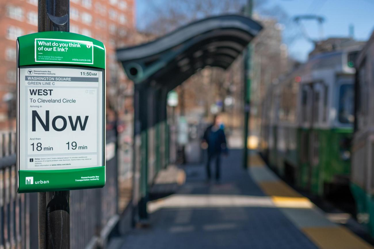 """Closeup of Green Line C e-ink sign at Washington Square, reading """"Now"""" west to Clevelant Circle, with some of a Green Line train in the background."""