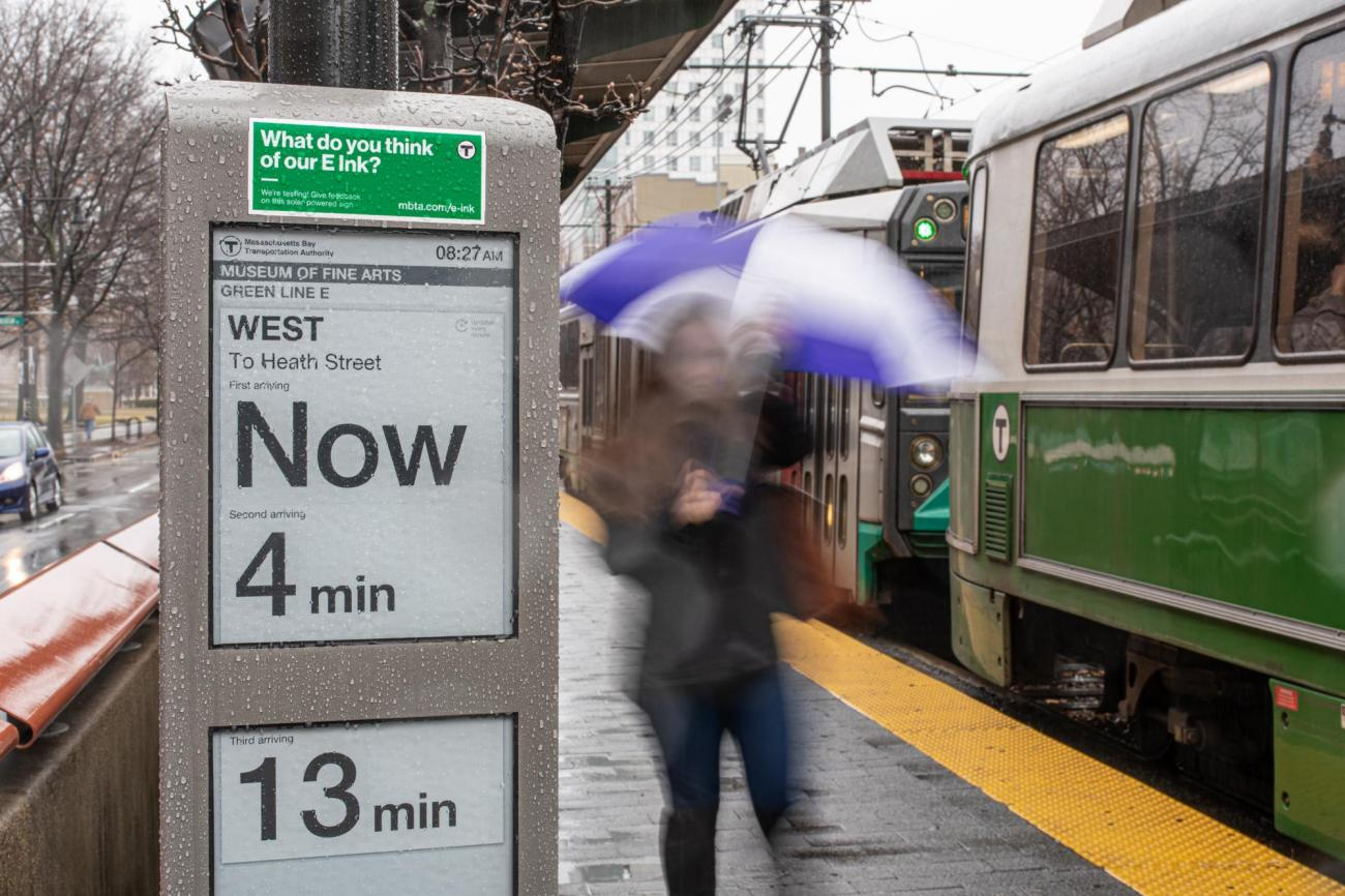 """Closeup of e-ink sign at MFA Station on the Green Line E branch. The sign reads """"West to Heath Street Now, Second arriving 4 min, Third arriving 13 min."""" In the background, a train is pulled up to the platform, and a rider with an umbrella walks past."""