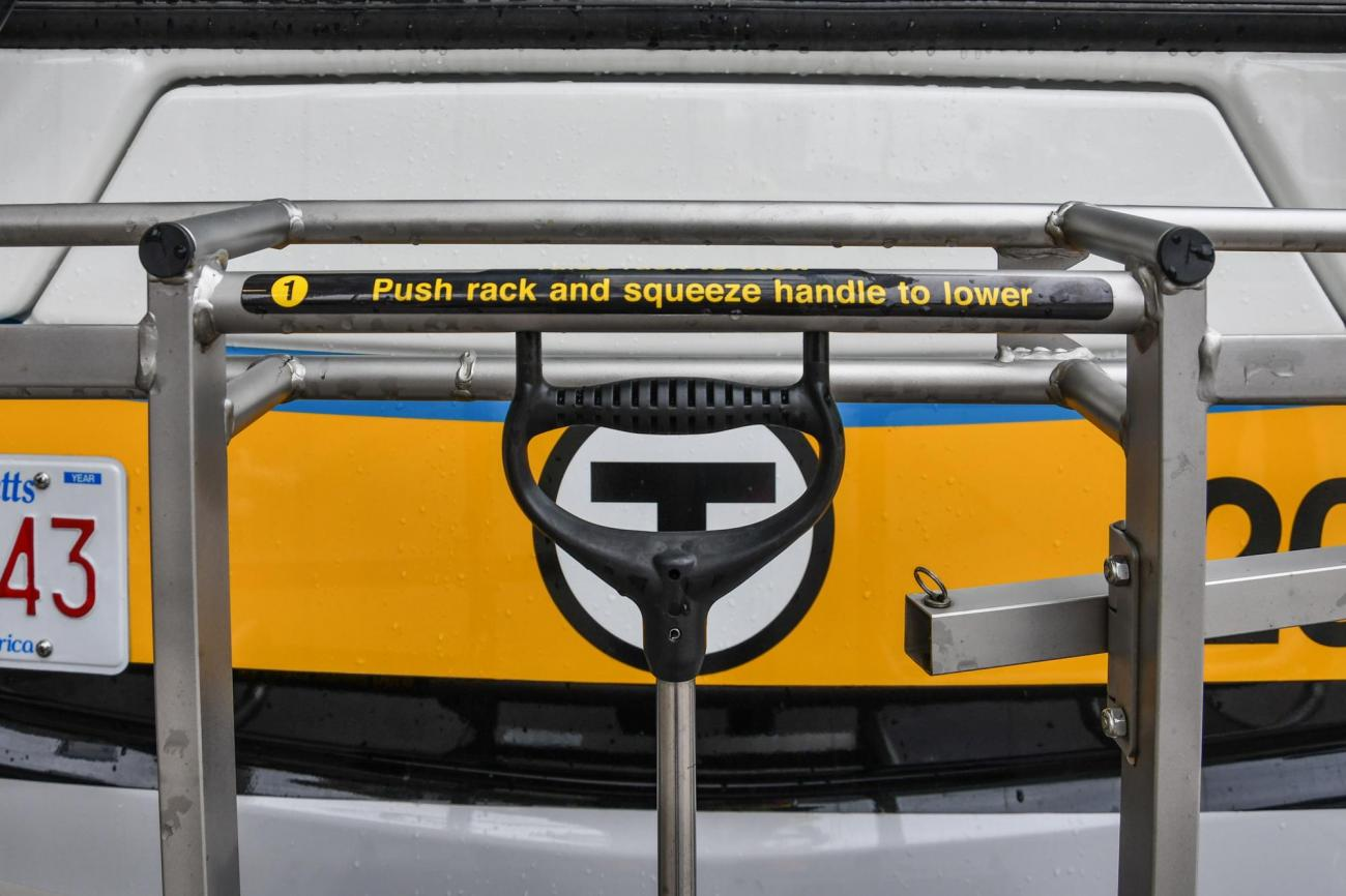 A bike rack on the front of a bus with instructions that say push rack and squeeze handle to lower