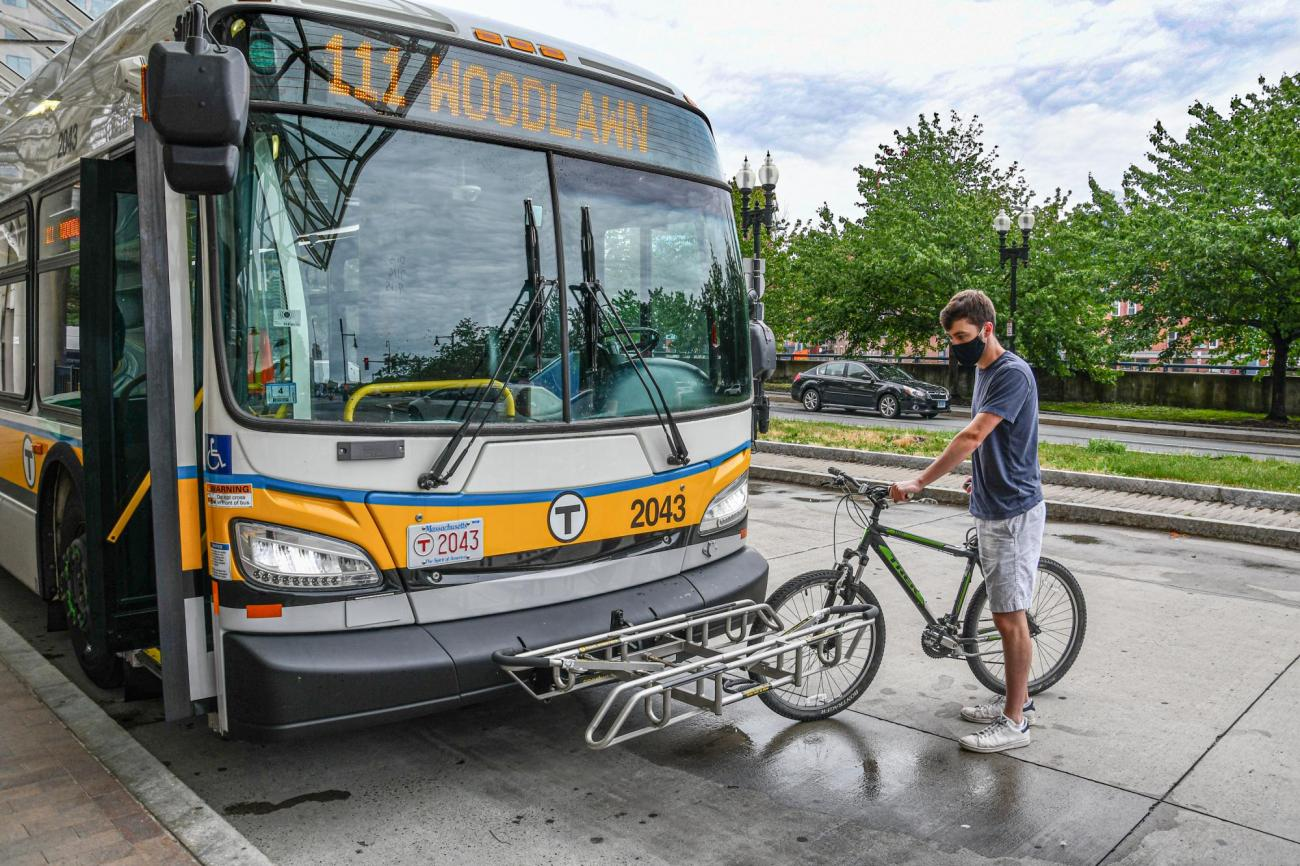 A man stands beside a bus with his bike, preparing to load it onto the bike rack