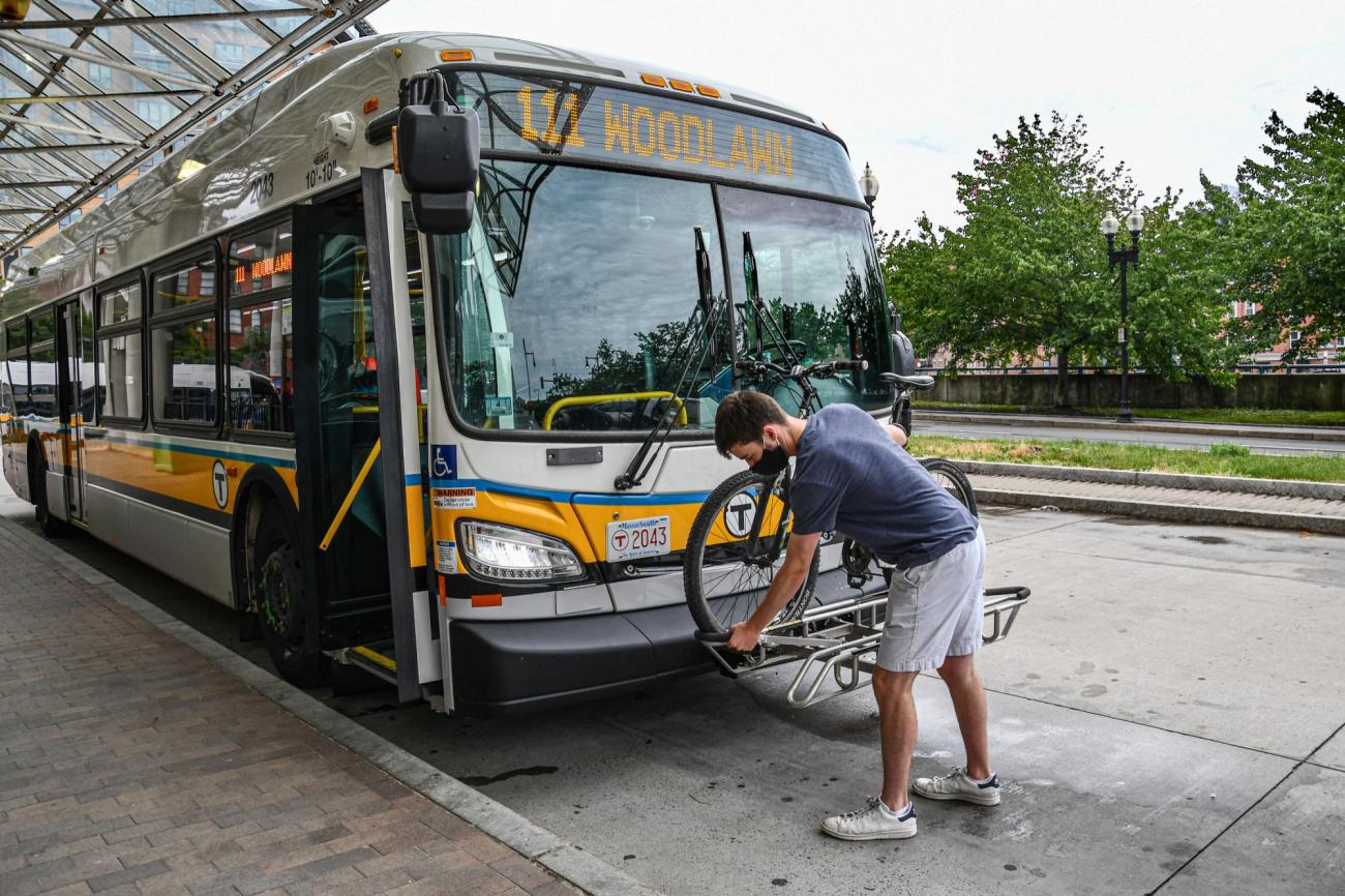 A man reaches for the securing bar to secure his bike in place on a bus bike rack