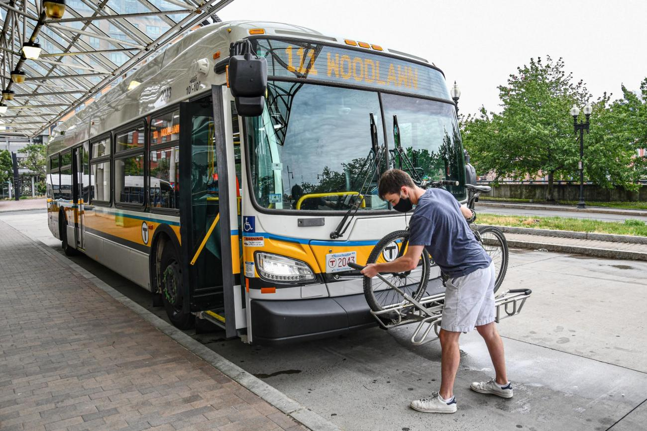 A man lifts the securing bar to secure his bike in place on a bus bike rack