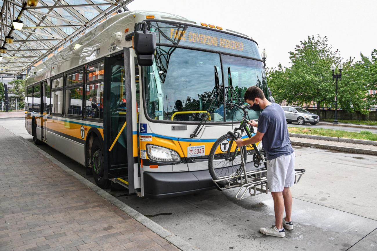 A man checks his bike to make sure it is secure in place on a bus bike rack