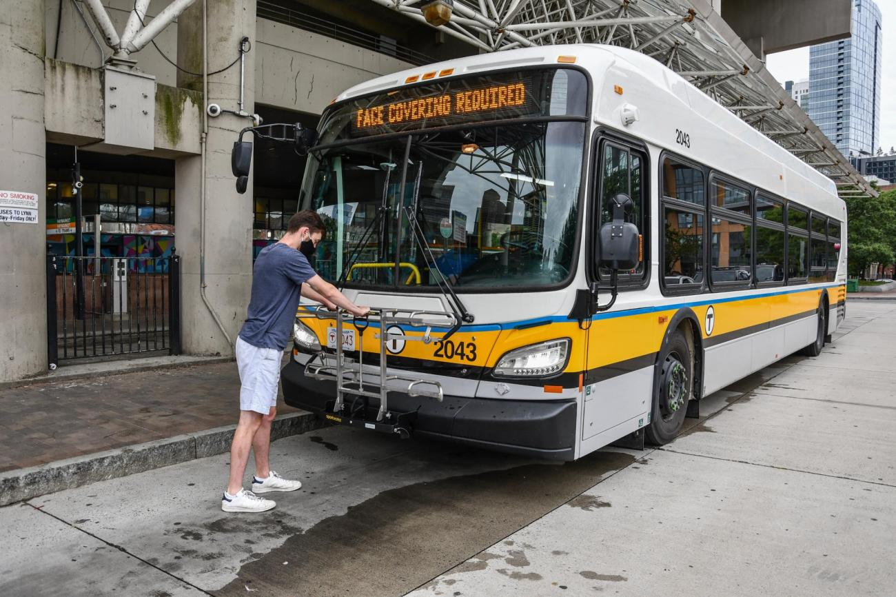 A person opens a bike rack on the front of a bus at Haymarket station