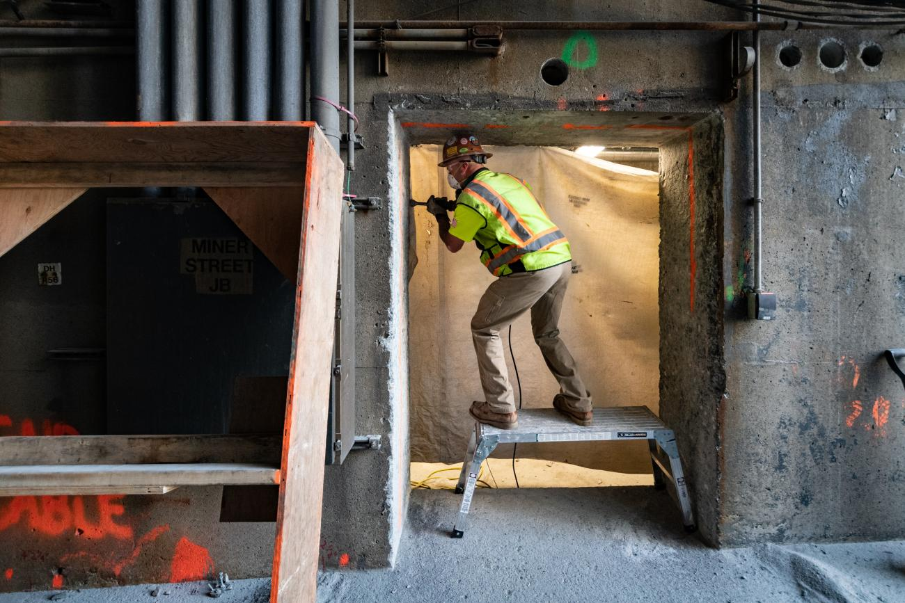 A crew member works on a floodgate at the Fenway Portal