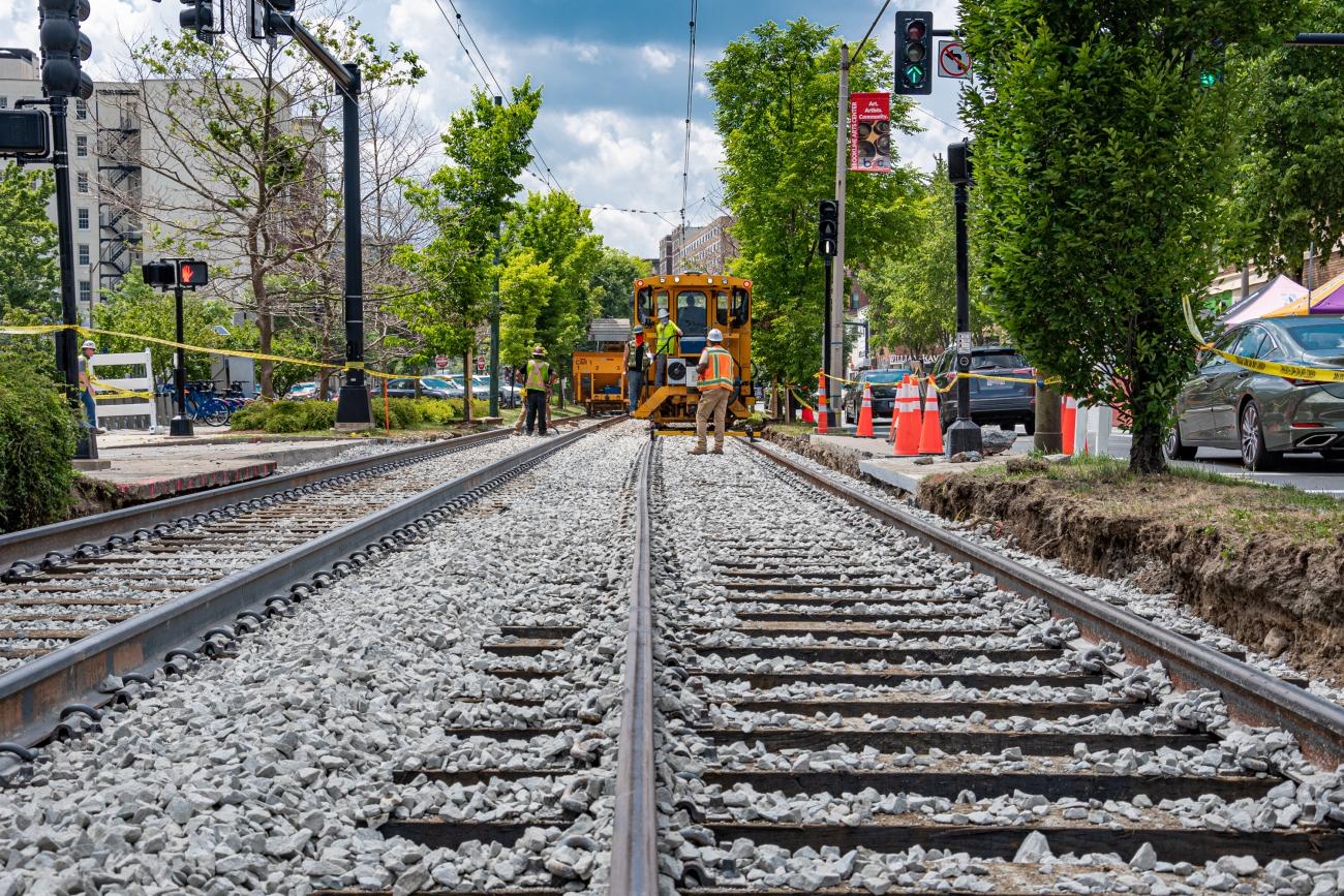 Machinery is used to align the tracks and install new stone ballast