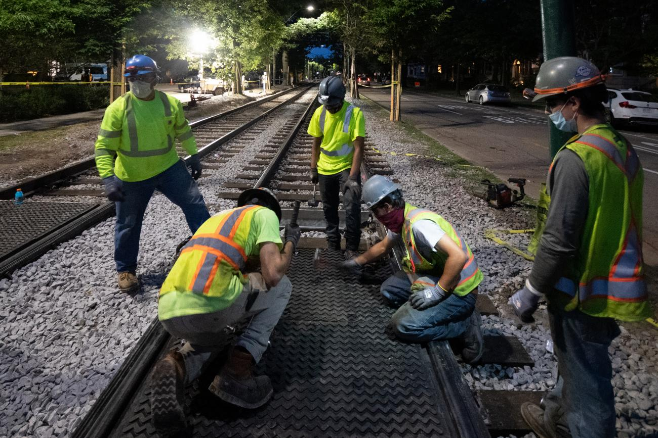 Crews installing metal rail crossing plates during overnight work on the Green Line C Branch