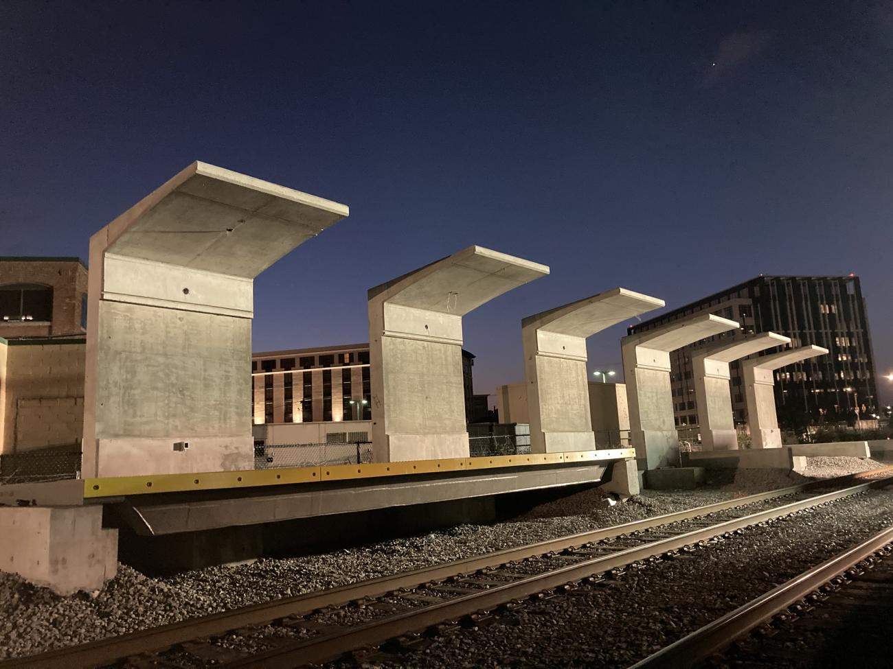 At night, partially installed train platforms and large concrete overhangs at the new Chelsea Commuter Rail station.