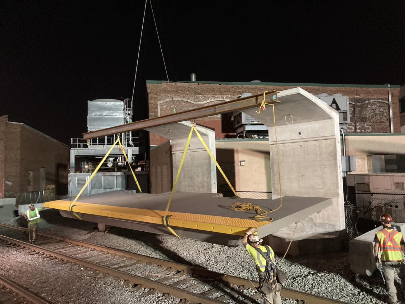 At night, workers guide a section of train platform into place at the new Chelsea Commuter Rail Station.