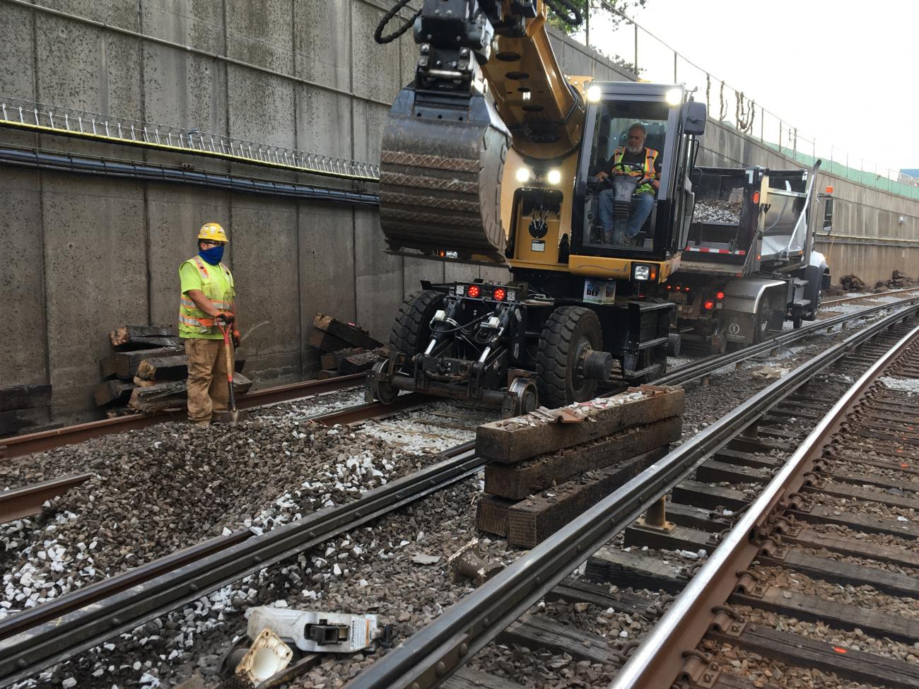 Two member construction crew works on railway tracks. A man uses heavy machinery to replace rail ties and remove rubble.