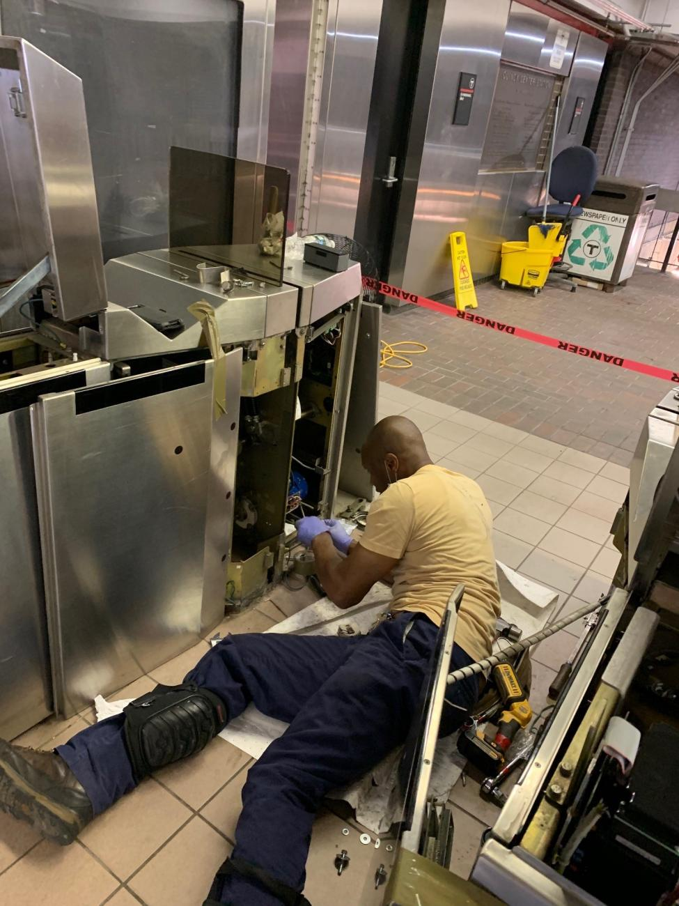 Man lays on the ground as he works to replace the fare gate at Quincy Center Station.