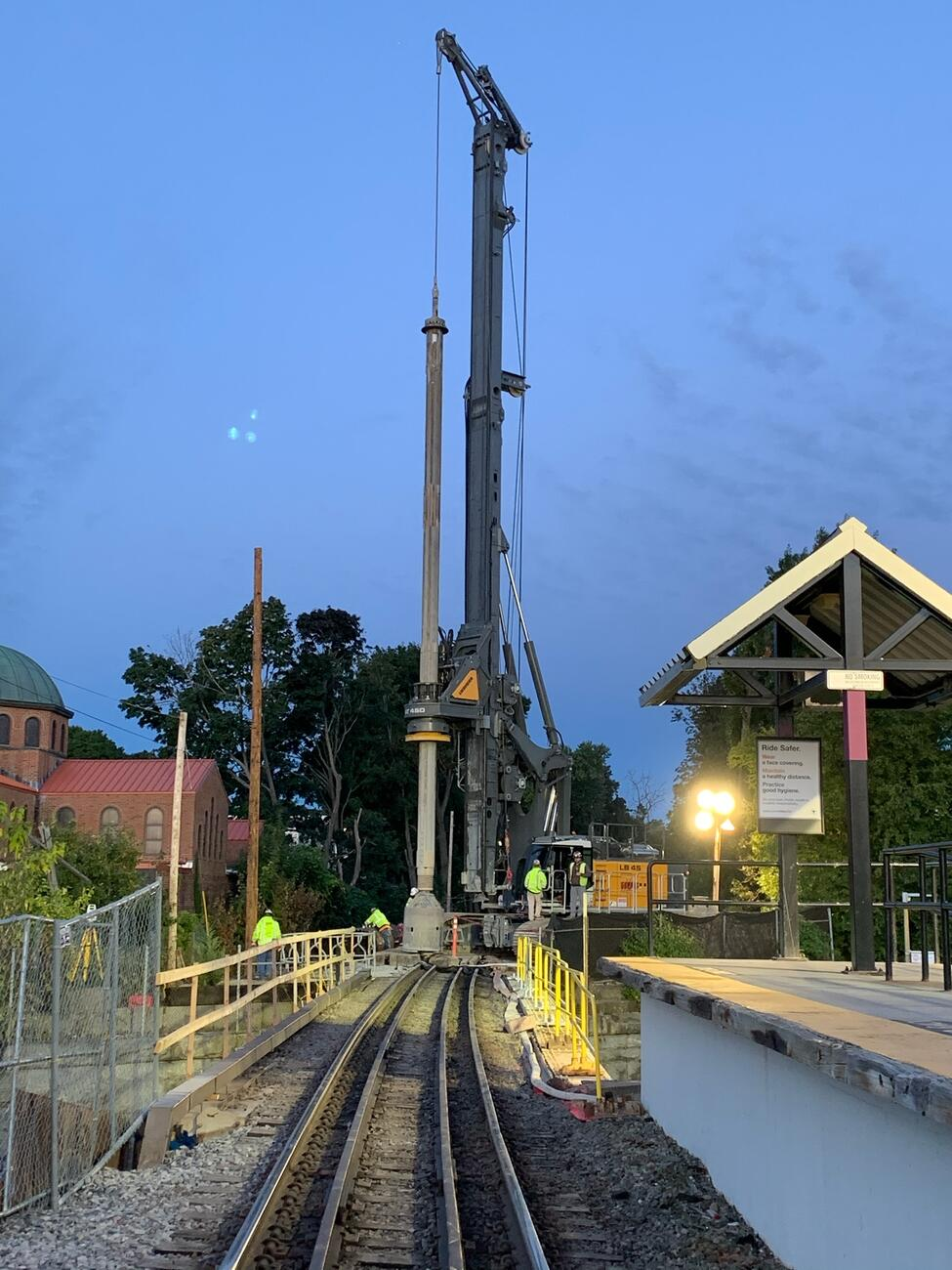 Image of the Robert Street platform at dusk. Drilled shaft prep work towers over residential buildings in the distance.
