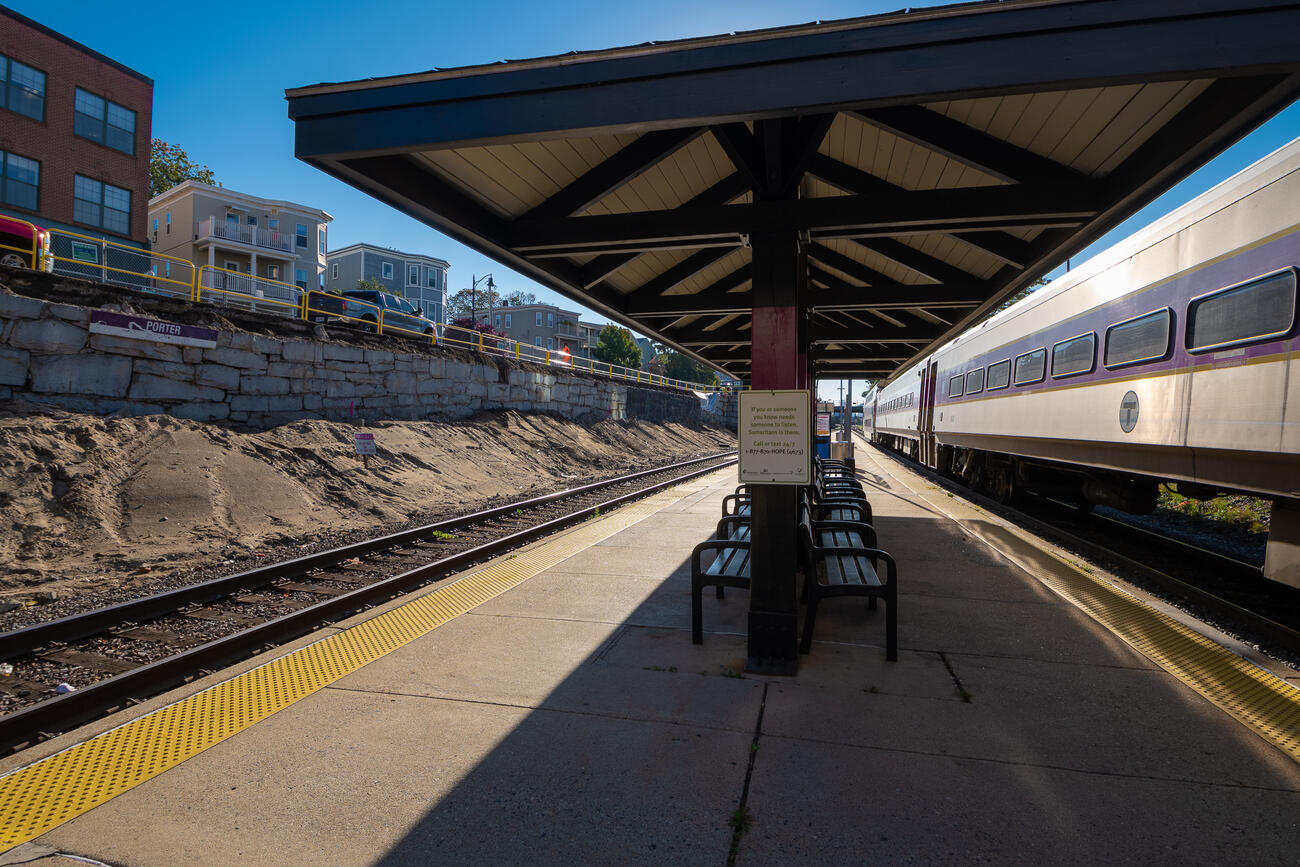 Empty Commuter Rail platform at Porter Square during a clear fall day. The Fitchburg train is seen going inbound, while the retaining wall under Somerville Ave is under construction.