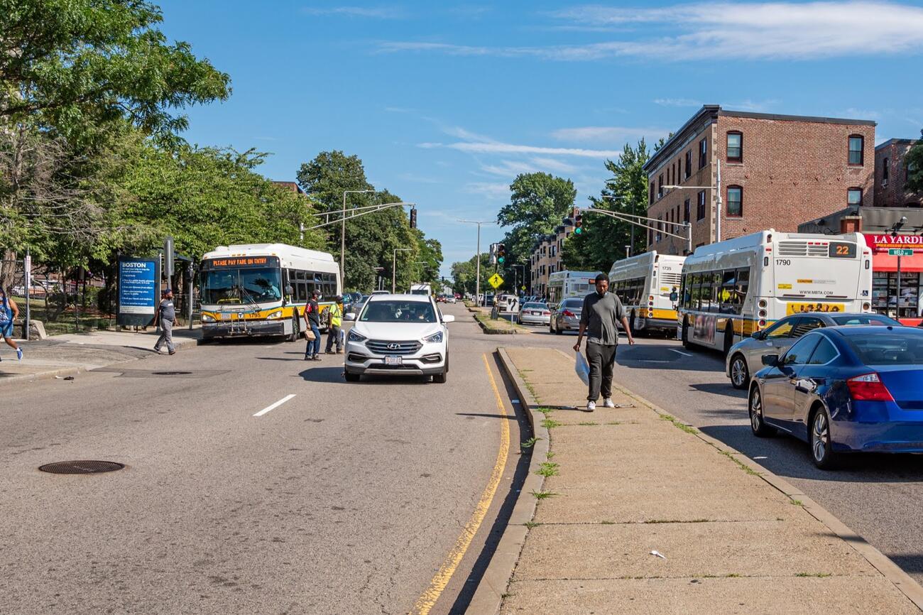 Pedestrians cross the street in front of the bus, but no crosswalk