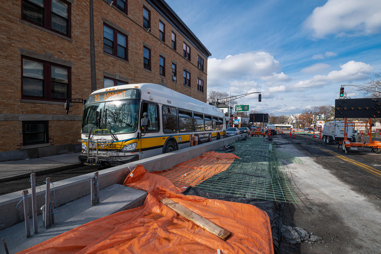 A Route 22 bus inbound to Ashmont passes by a new concrete bus boarding platform under construction near the intersection of Columbus Ave and Dixwell St near Egleston Square. The concrete platform is separate from the sidewalk, located between one traffic lane and a future bus lane under construction and is approximately 9 inches tall relative to the surface of the road and 9 feet wide, currently half-complete with exposed rebar visible.