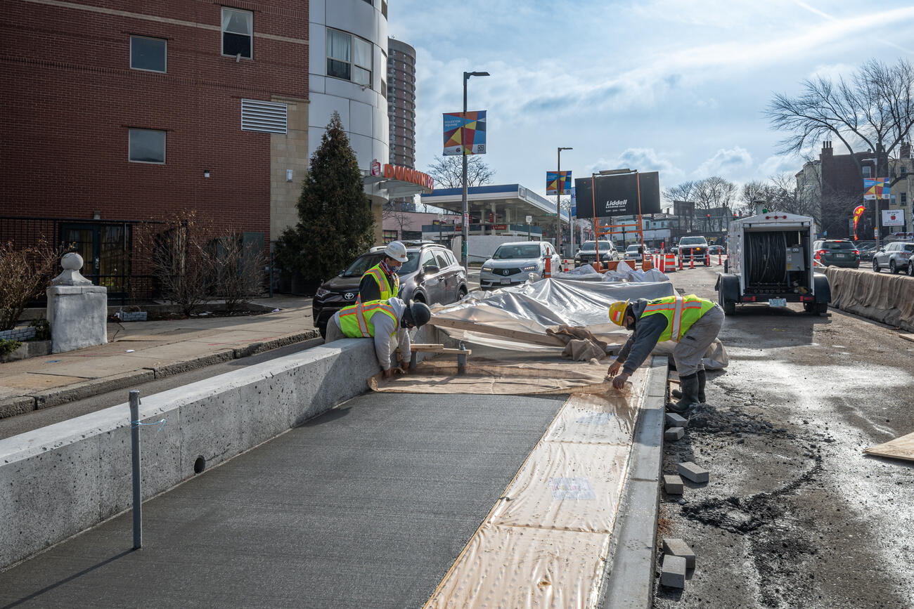 Three construction crew members work on the new bus boarding platform on Columbus Ave at Bray St near Egleston Square. The concrete boarding platform is separate from the sidewalk, located between one traffic lane and a future bus lane under construction. The platform is approximately 9 inches tall relative to the surface of the road and 9 feet wide, and currently half-complete with exposed rebar visible.
